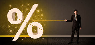 Business man pulling rope with big procent symbol sign Stock Photography
