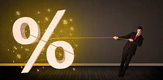 Business man pulling rope with big procent symbol sign Royalty Free Stock Image