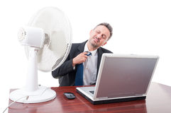Business man pulling tie in front of ventilator Stock Photography