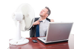 Business man pulling tie in front of ventilator Royalty Free Stock Image