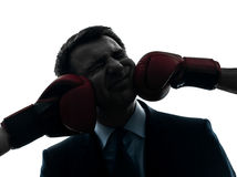 Business man punch by boxing gloves silhouette Stock Photo