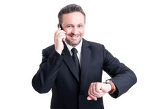 Business man with punctuality. Checking the watch while talking on the phone royalty free stock images