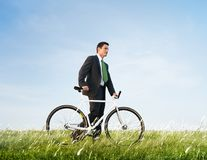 Business Man Pushing Bike Outdoors Concept royalty free stock images