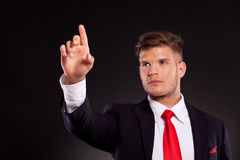 Business man pushing button. Young business man pushing an imaginary button and looking to it, on dark background Royalty Free Stock Photo