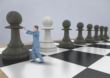 Business man pushing chess piece against grey wall Stock Image