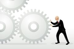 Business Man Pushing Cog Wheel Stock Image