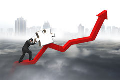 Business man pushing 3D jigsaw puzzle upward red trend line Stock Photography
