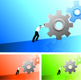 Business man pushing gears uphill Royalty Free Stock Images