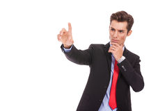 Business man pushing imaginary digital button. Young business man pushing imaginary digital buttons. Cool serious businss man Royalty Free Stock Images