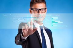 Business man  pushing some buttons. Business man  pushing some business graphs on a touch screen interface Royalty Free Stock Photography