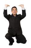 Business man pushing something up Stock Image