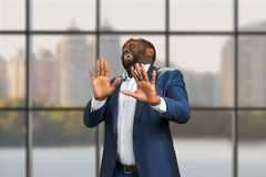 Business man put his hands forward. Black manager with emotion of fear on blurred background. Surprised and scared businessman Royalty Free Stock Photos
