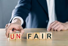Business man puts away first two letters from the word unfair, so it becomes fair; sports or business fair play concept stock image