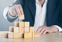 Business man puts next stone on complex structure made from wooden blocks; career or achievement or complex project management. Concept, blue toned with ligth stock images