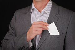 Business man putting a blank business card in his suit pocket. Closeup of a businessman taking a business card from the breast poc Stock Photography