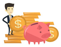Business man putting coin in piggy bank. Young asian business man saving money in piggy bank. Successful business man putting money in big pink piggy bank Royalty Free Stock Images