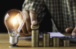 Free Business Man Putting Coin With Light Bulb On Table For Saving Bank And Account For His Money All In Finance Accounting Concept Royalty Free Stock Image - 139175026