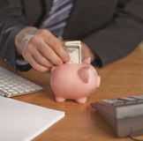 Business man putting money in Piggy bank Royalty Free Stock Photo