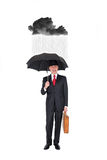 Business man with a rainy black cloud over him Royalty Free Stock Photo