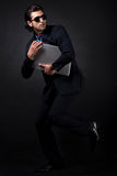 Business man raise his left leg. With laptop in studio royalty free stock photography