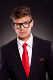 Business man with raised eyebrow. Portrait of a young business man looking at the camera with raised eyebrow, on dark background Royalty Free Stock Photo