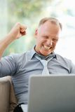 Business man raising fist using laptop Stock Image