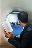 Business man reading book in passenger plane seat and looking to Stock Photo
