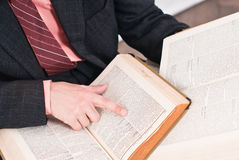 Business man reading books. Business man reading paragraphs from books with finger on the page standing at the office Stock Photo