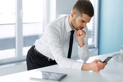 Business Man Reading Something on the Screen of His Cell Phone Stock Photography