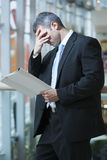 Business man reads document and covers face Royalty Free Stock Photography