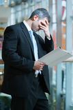 Business man reads document and covers face Royalty Free Stock Photos