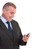 Business man reads something on phone and laughs Royalty Free Stock Photography