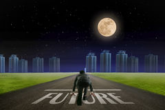 Business man ready to run Future line in front of city. Night ba. Ck view. Elements of this image furnished by NASA Stock Photos