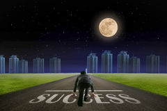 Business man ready to run SUCCESS line in front of city. Night b Royalty Free Stock Photos