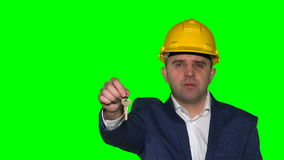 Business man or real estate agent with helmet show keys from new house or flat stock video footage
