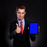 Business man recommends tablet. Portrait of a young business man standing against a black background presenting a tablet and showing thumbs up sign while smiling Stock Photography