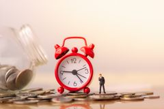 Business man and red alarm clock on stack of coins in concept of savings and money growing or energy save. royalty free stock photography