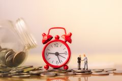 Business man and red alarm clock on stack of coins in concept of savings and money growing or energy save. stock image