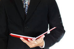 Business man and red book. Business man reading the red book Royalty Free Stock Photography