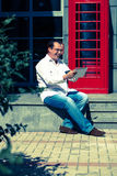 Business man on  red classic English telephone box Royalty Free Stock Image