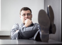 Business man. Relaxed casual young business man with legs on desk in office. Shallow depth of field Stock Image