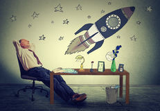 Business man relaxing at his desk in office daydreaming of space tourism Royalty Free Stock Images