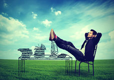 Business man relaxing at his desk outdoors in the middle of a green meadow. Happy business man relaxing at his desk outdoors in the middle of a green meadow Royalty Free Stock Photography