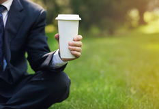 Business man relaxing in a park drinking black coffee Royalty Free Stock Image