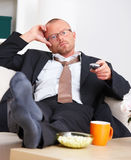 Business man relaxing on a sofa using remote Stock Photos