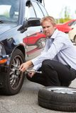Business Man Replacing Tire. Unhappy business man replacing tire on car royalty free stock images