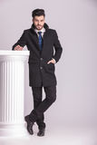 Business man resting his hand on a white column. Royalty Free Stock Photography
