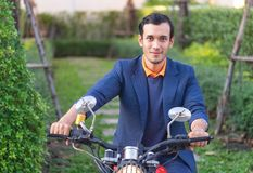 Business man riding a motorbike in the park royalty free stock photo
