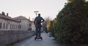 Business man riding segway in city commuting to work or home while calling using smartphone.Modern future transport. Technology.Sidewalk urban outdoor.Warm stock footage