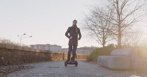 Business man riding segway in city commuting to work or home while calling using smartphone.Modern future transport. Technology.Sidewalk urban outdoor.Warm stock video footage